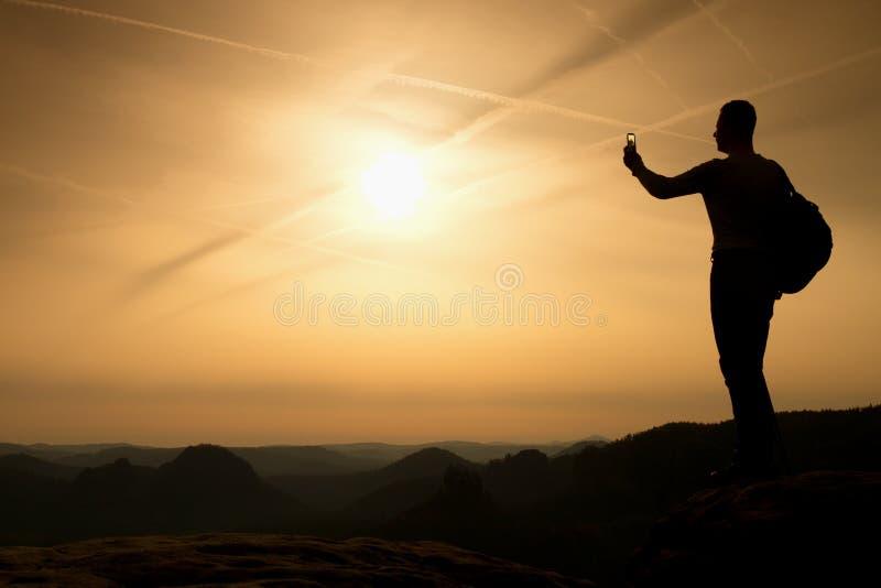 有电话的高背包徒步旅行者在手中 在山的春天破晓 库存照片