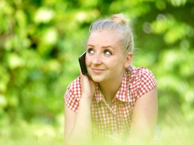 有电话的年轻可爱的妇女 免版税库存照片