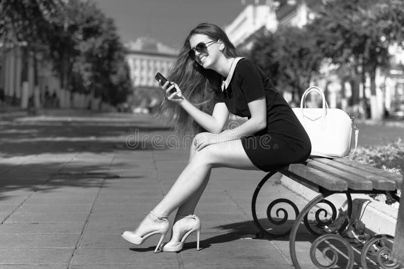 有电话的年轻女实业家坐 库存图片