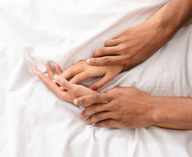 有男人和妇女的手在床上的性 免版税库存照片
