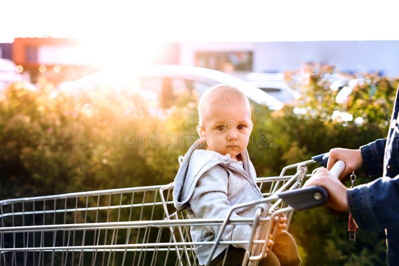 有男婴去的购物的母亲在停车场 免版税库存照片