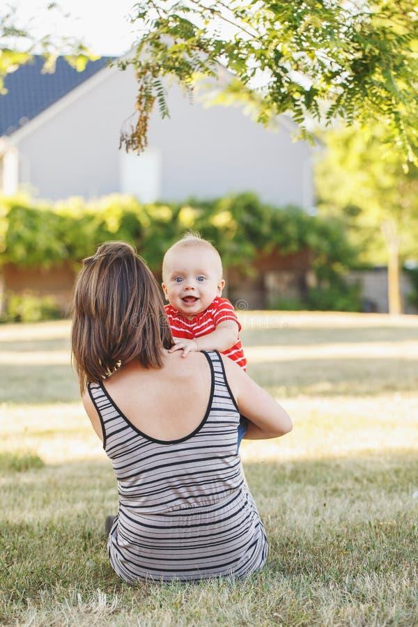 有男婴的白种人母亲红色T恤杉的在外面领域草甸 图库摄影