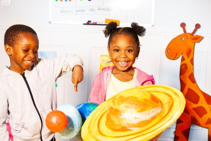 有男孩的小黑人女孩学会戏剧行星模型 库存照片
