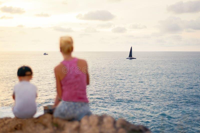 有男孩的少妇坐峭壁在晴朗的岸在水附近和享受日落 免版税图库摄影
