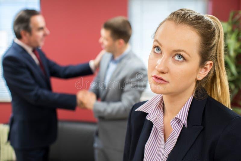 有男性同事的不快乐的女实业家祝贺 免版税库存照片