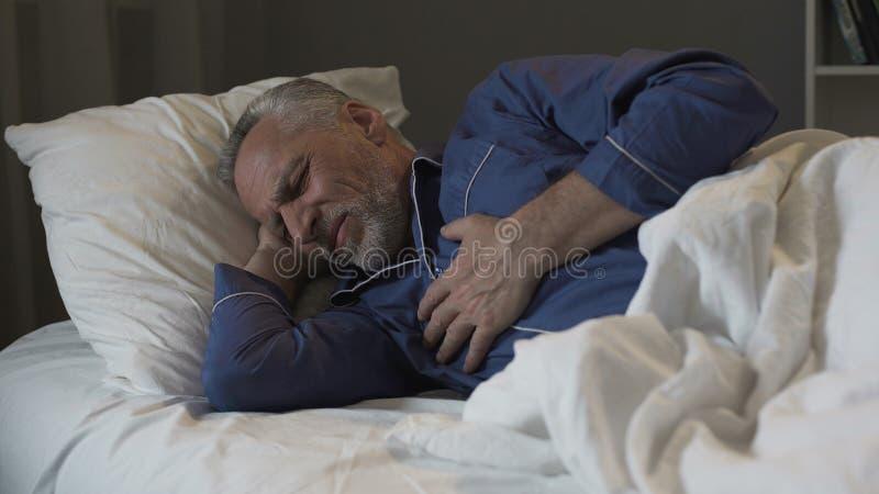 有男性的领抚恤金者心脏病发作,遭受的锋利的胸口痛,当睡觉时 免版税图库摄影