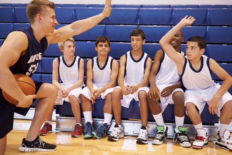 有男性高中的蓝球队与教练的队谈话 免版税库存照片