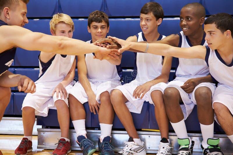 有男性高中的蓝球队与教练的队谈话 免版税库存图片
