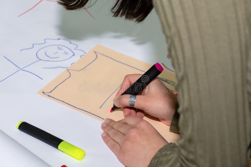 有画在大白皮书的蓝色感觉的笔的学生手简单的stickman在书桌上在教室 免版税库存图片