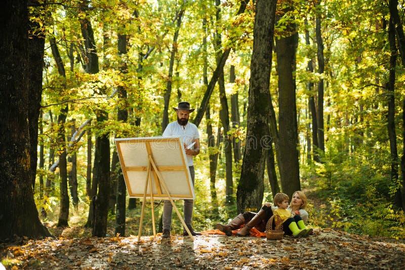 有画架和帆布的画家 有一个胡子的行家艺术家在创造艺术的帽子在森林 r 绘  免版税库存图片