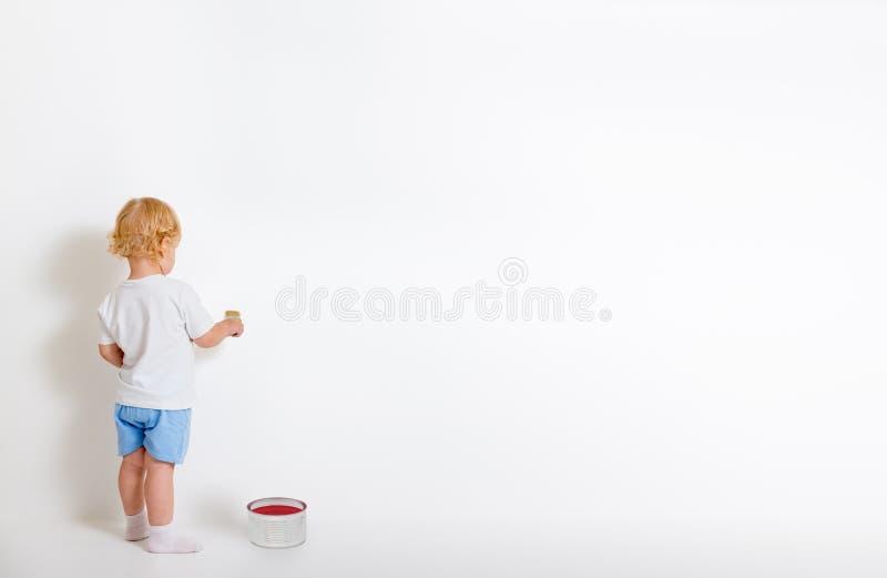 有画笔的小男孩和站立在白色墙壁附近的锡罐 免版税库存照片