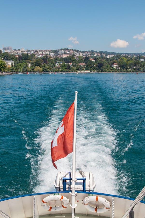 有留下Ouchy的洛桑港瑞士旗子的客船在湖Leman日内瓦湖,瑞士在晴朗美好的夏天 免版税图库摄影