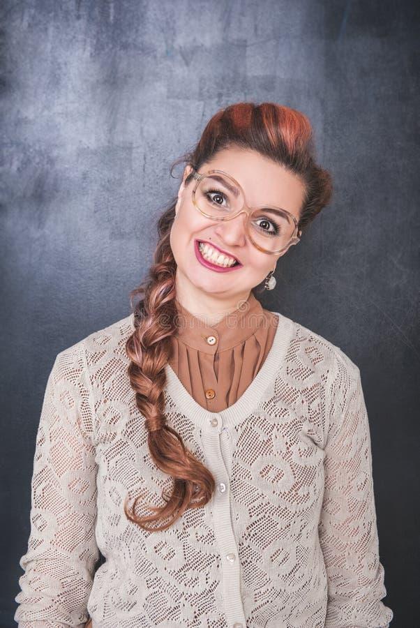 有疯狂的鬼脸的微笑的妇女在黑板背景 免版税图库摄影
