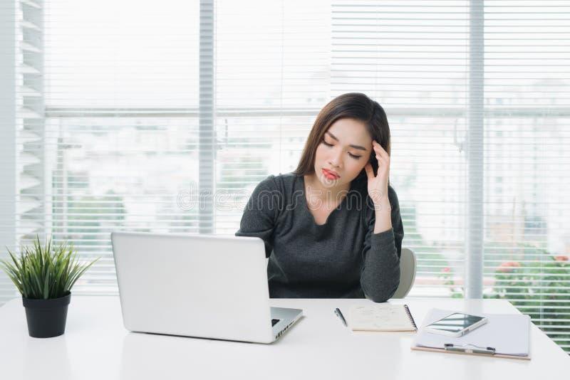 有疲乏的眼睛和头疼的年轻亚裔女商人 免版税库存照片