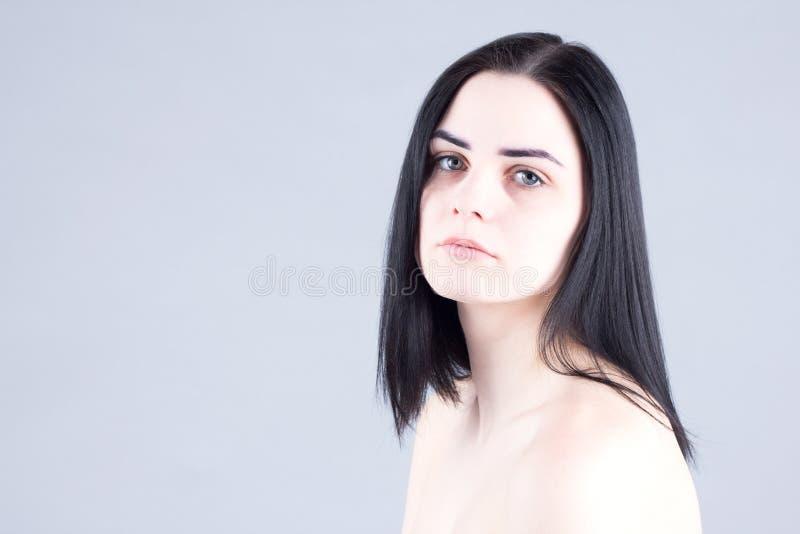 有疲乏的眼睛的不快乐的妇女 库存照片