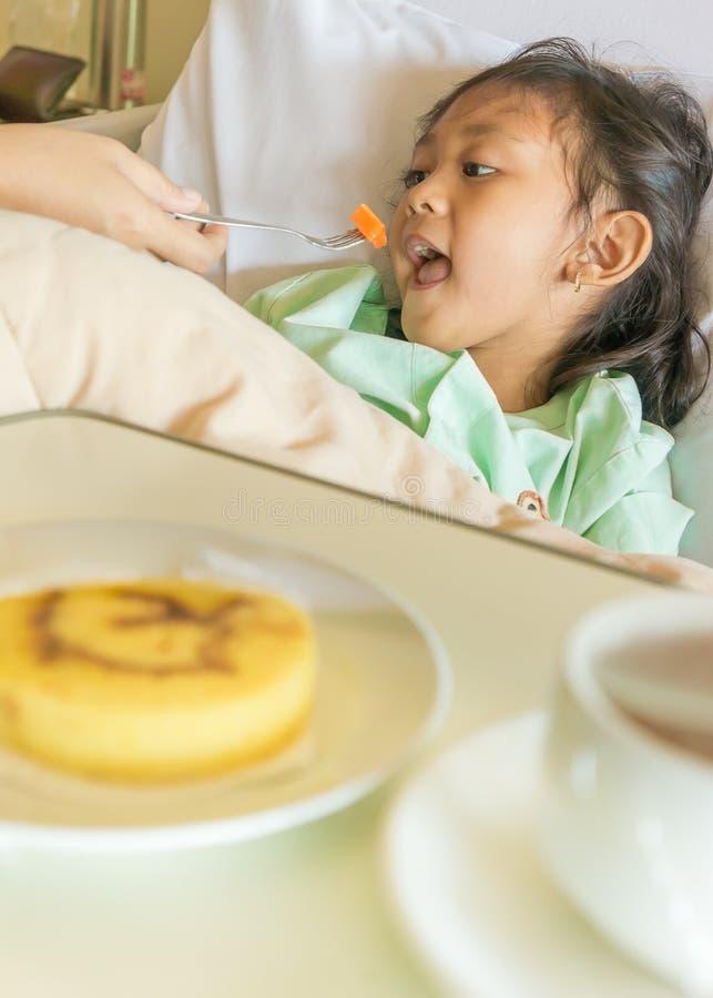 有病的亚裔儿童医院的患者在床上的膳食 免版税库存图片