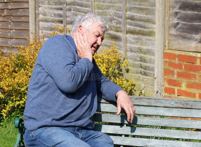 有痛苦的受伤的脖子的老人 免版税图库摄影