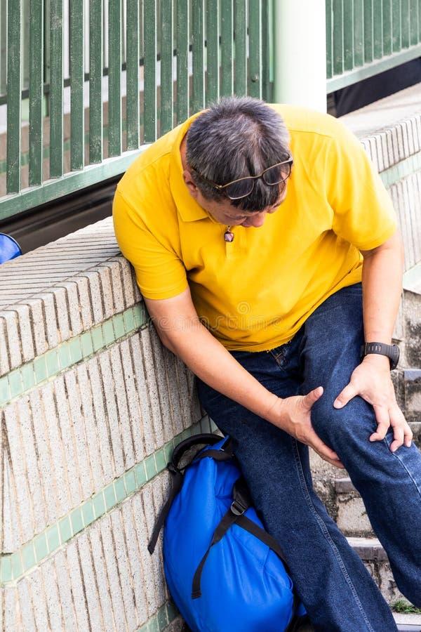有痛苦的膝盖奋斗的人步行沿着向下阶梯步级的 库存图片