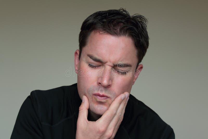 有痛苦的面孔的年轻人由于牙痛 图库摄影
