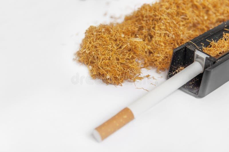 有瘾堆的一台香烟滚轧机烟草 免版税图库摄影