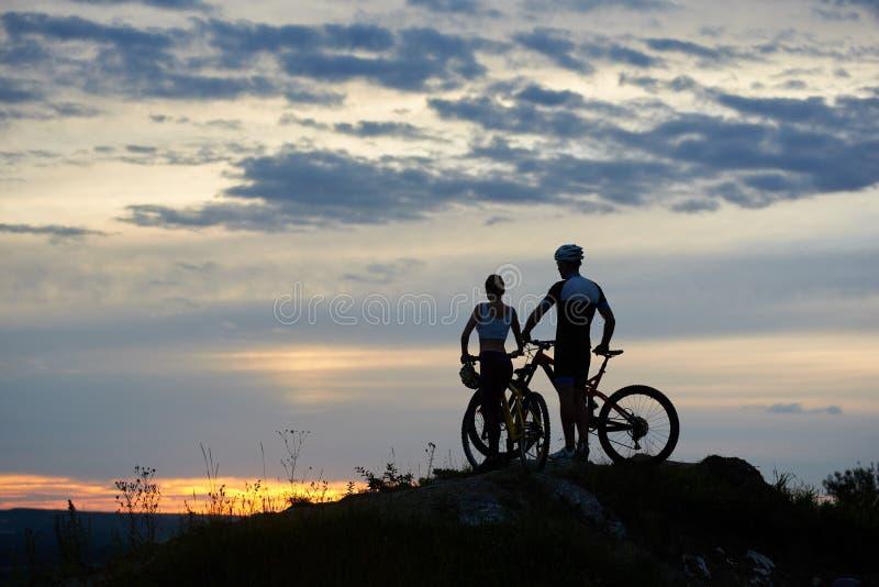 有登山车的背面图两青年人站立在与美好的风景的峭壁顶部在日落 库存图片