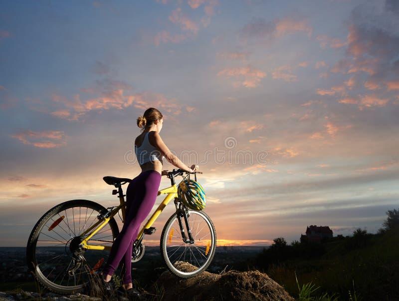 有登山车的苗条妇女在小山站立在美丽的天空下在日落 免版税库存照片