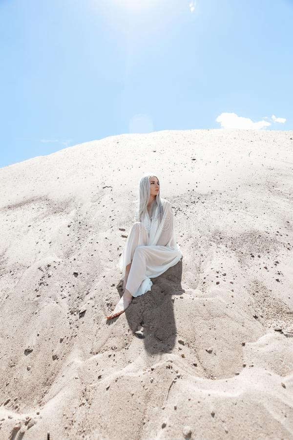 有白发的女孩在沙子山中 免版税库存照片