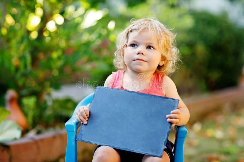 有白垩书桌的愉快的矮小的小孩女孩在手上 举行的copyspace的健康可爱的户外儿童空的书桌  图库摄影