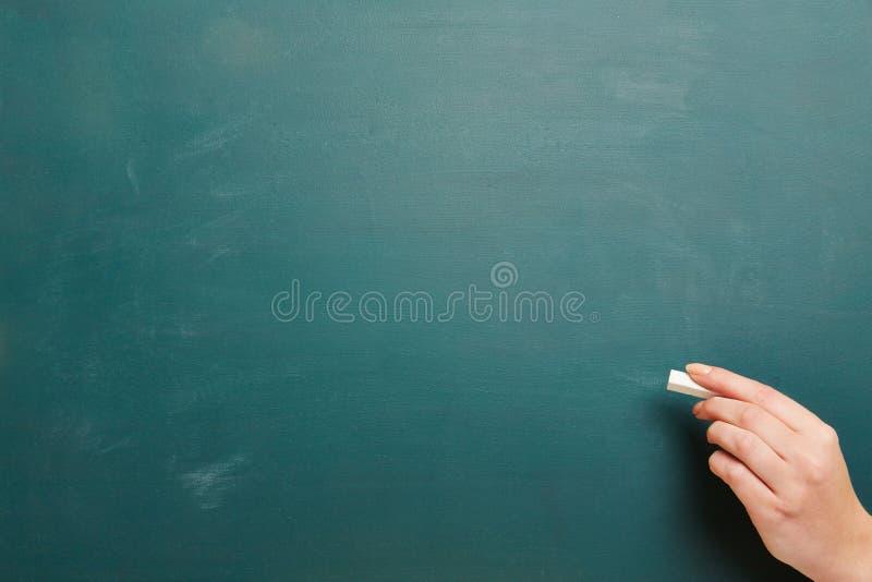 有白垩和绿色黑板的手 库存照片