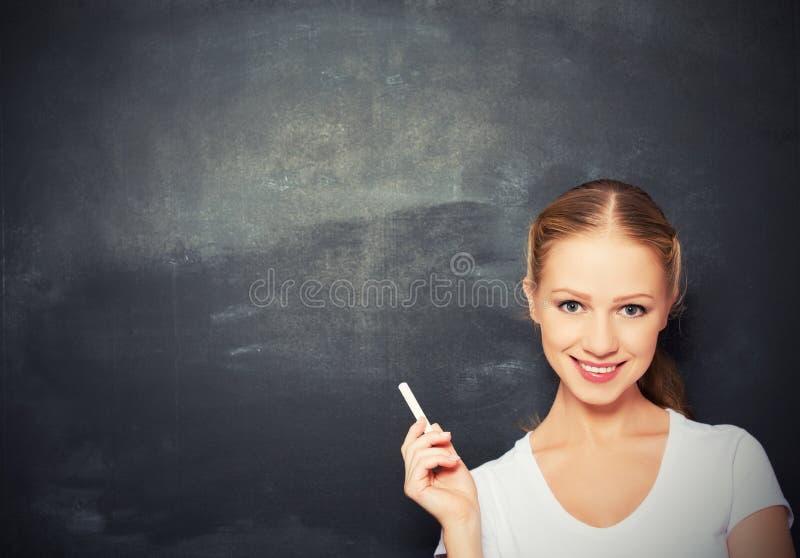 有白垩的妇女在空的黑板 免版税库存图片