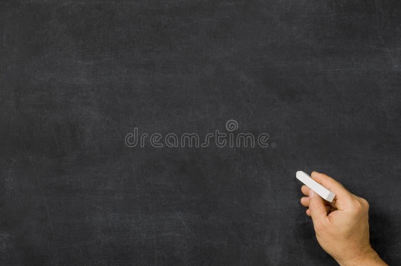 有白垩的手在黑板前面 免版税库存图片