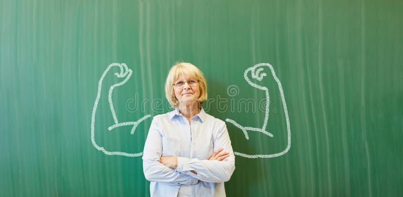 有白垩肌肉的坚强的资深老师 免版税库存图片