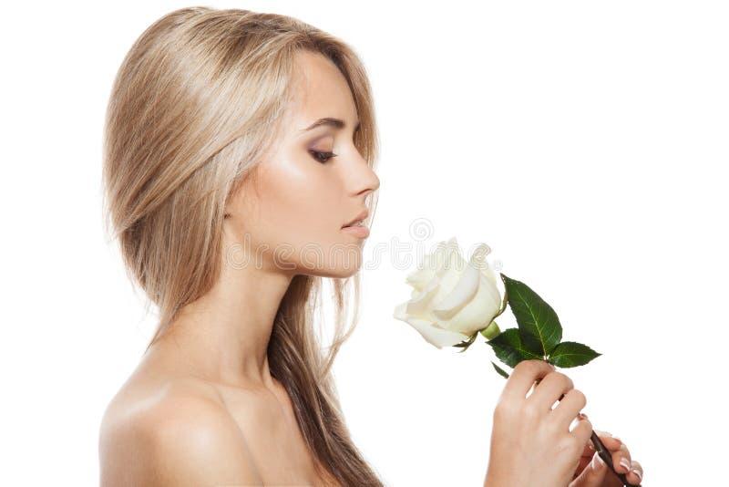 有白玫瑰的美丽的白肤金发的女孩 图库摄影