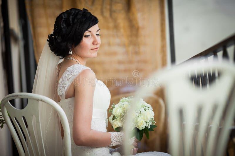 有白玫瑰花束的美丽的深色的新娘在典雅的dre 库存照片