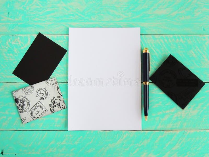 有白皮书、专业笔、卡片和信封的被称呼的桌面,在木背景 免版税图库摄影