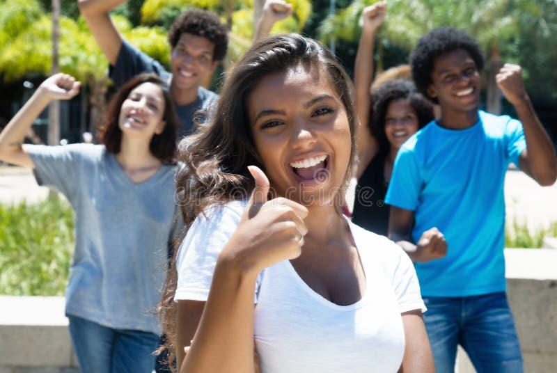 有白种人和非裔美国人的人的欢呼的拉丁妇女 免版税库存图片