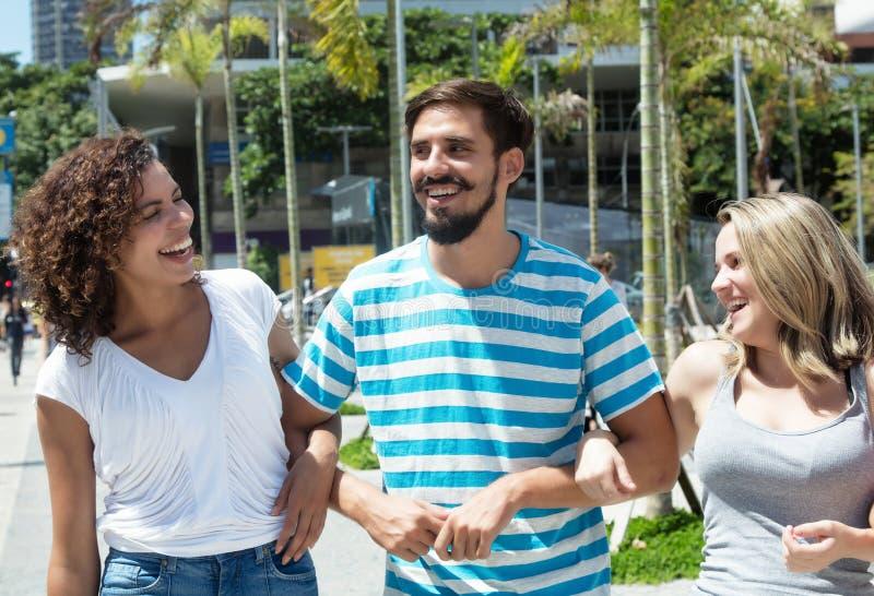 有白种人妇女和拉美裔女朋友的笑的拉丁人 免版税图库摄影