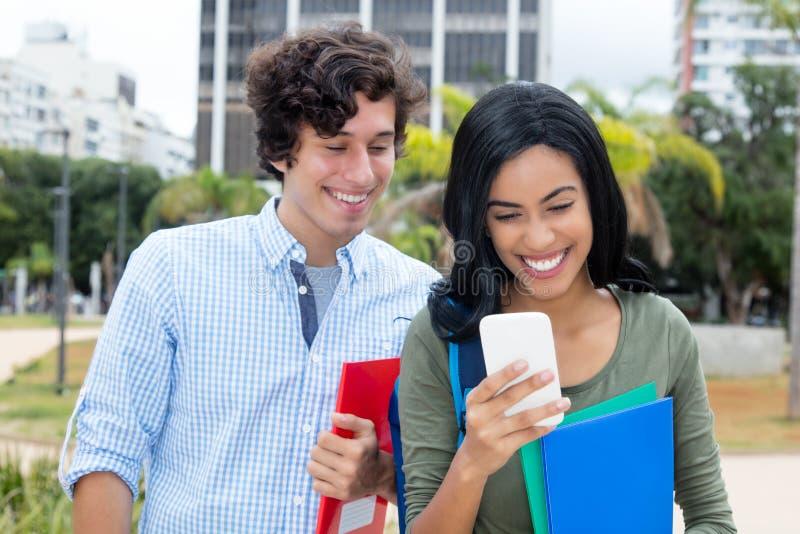有白种人年轻成人人和电话的印度妇女 库存照片