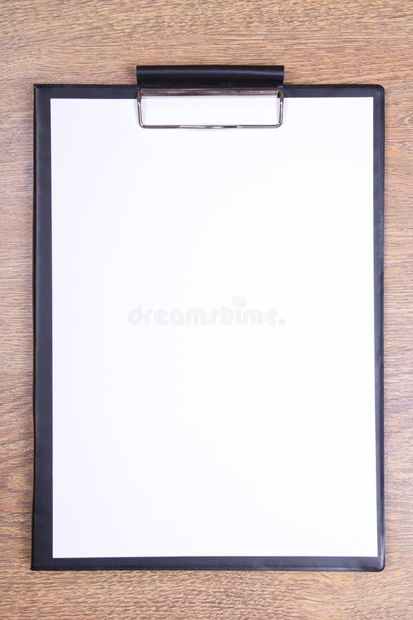 有白纸的剪贴板在木桌上 图库摄影