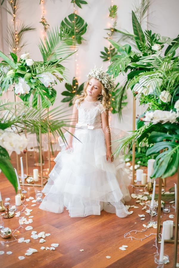 有白肤金发的卷发在一套白色婚礼礼服和花花圈的逗人喜爱的小女孩在花卉装饰的 免版税库存照片