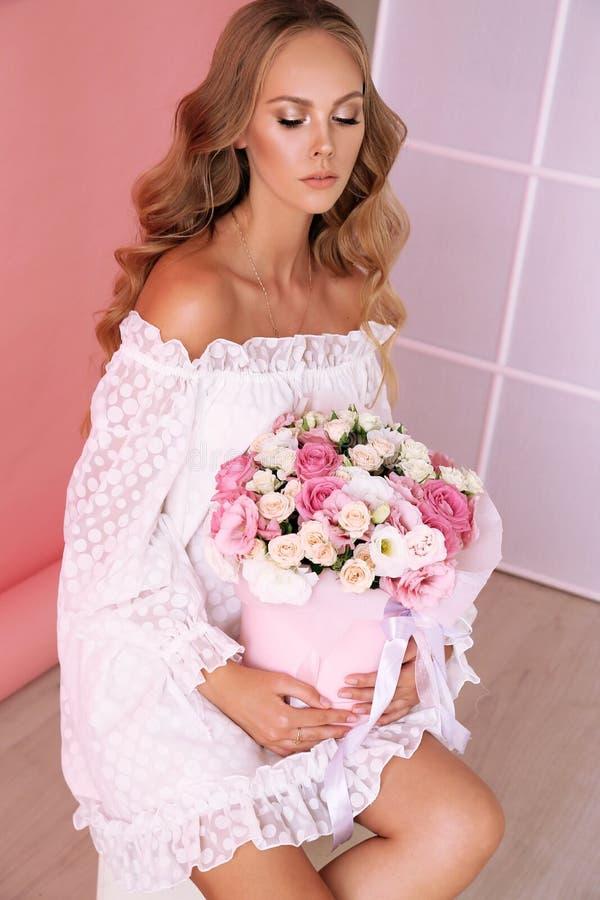 有白肤金发的卷发的美丽的年轻女人在摆在与春天花花束的典雅的衣裳  免版税库存图片