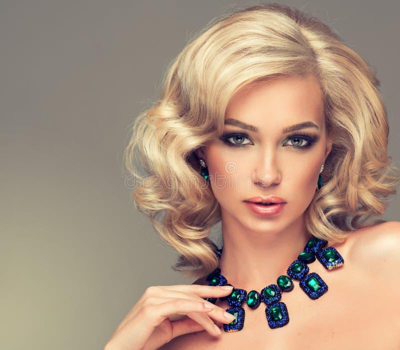 有白肤金发的卷发的美丽的逗人喜爱的女孩 免版税库存图片