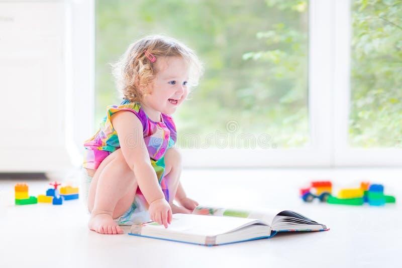有白肤金发的卷发阅读书的逗人喜爱的小孩女孩 免版税库存照片