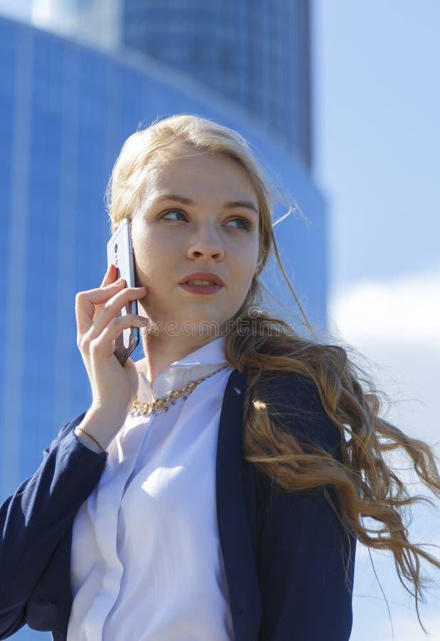 有白肤金发的女实业家企业电话 与高大厦的欧洲妇女身分外部在背景 免版税库存照片