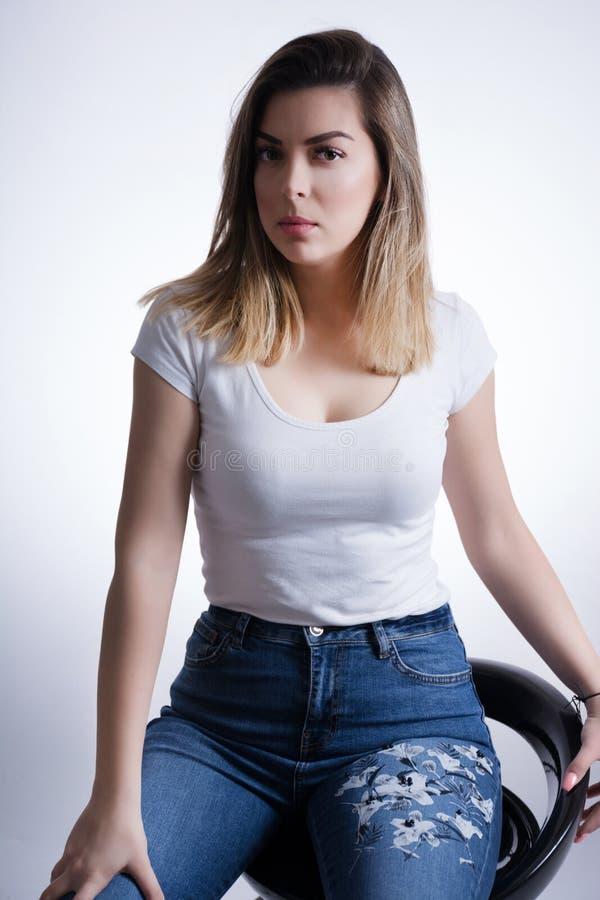 有白肤金发的棕色头发的女孩在蓝色牛仔裤坐一个高凳和摆在演播室 免版税库存图片