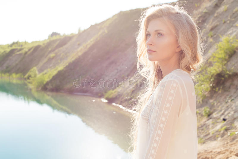 有白肤金发的波浪发的美丽的软的聪慧的女孩在湖的岸站立在日落在一个明亮的晴天 免版税库存图片
