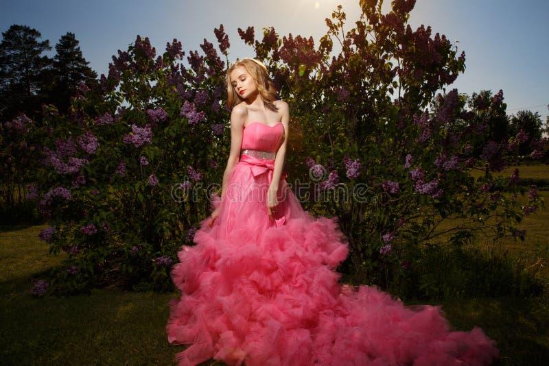 有白肤金发的波浪发的美丽,壮观的穿与蓬松裙子的女孩和构成桃红色晚礼服摆在得户外 免版税库存照片