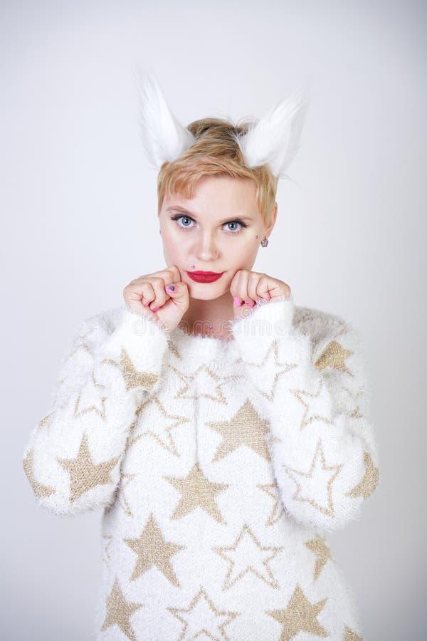 有白肤金发的短发和弯曲的正大小身体佩带的白色毛线衣的俏丽的逗人喜爱的亲切的女孩有金黄星和蓬松毛皮猫的e 库存图片