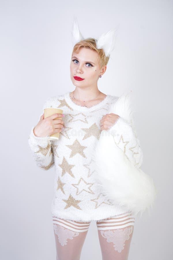 有白肤金发的短发和弯曲的正大小身体佩带的白色毛线衣的俏丽的逗人喜爱的亲切的女孩有金黄星和蓬松毛皮猫的e 免版税图库摄影