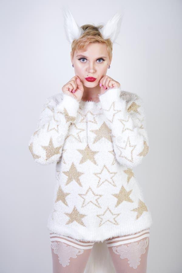 有白肤金发的短发和弯曲的正大小身体佩带的白色毛线衣的俏丽的逗人喜爱的亲切的女孩有金黄星和蓬松毛皮猫的e 库存照片